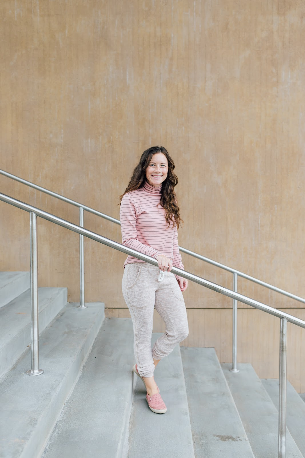 Fall outfit with pink turtleneck, tan joggers, and pink slip on sneakers on Caitlin Houston