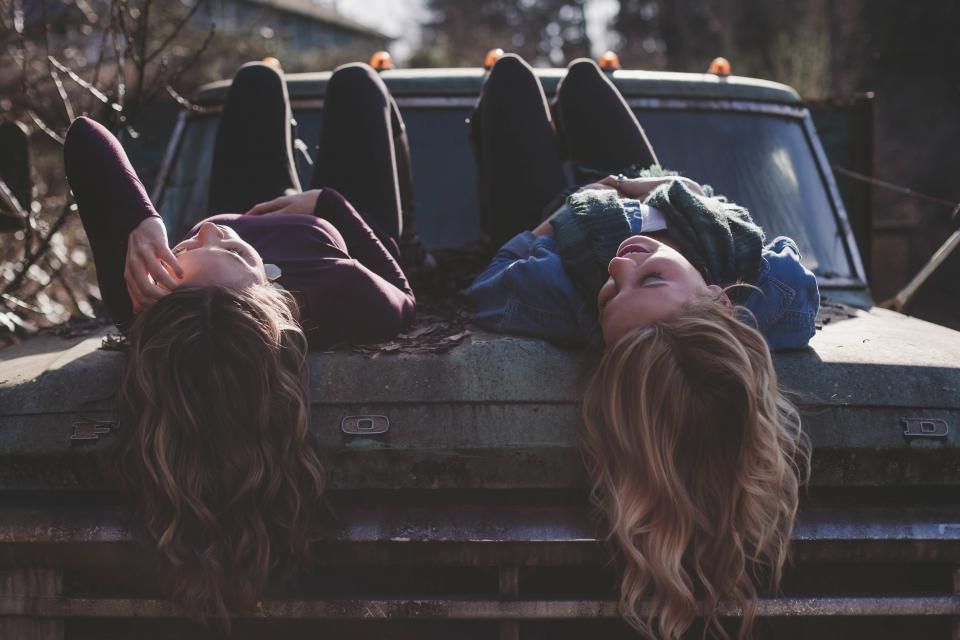 Be timeless: 2 young female friends face up lying on bonnet of old truck.