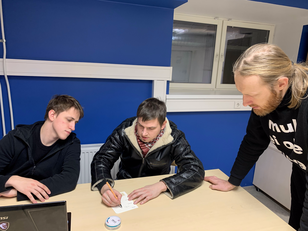 A group of people sitting at a table looking at a paper  Description automatically generated with low confidence