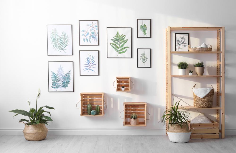 Uma parede com muitos quadros e plantas.