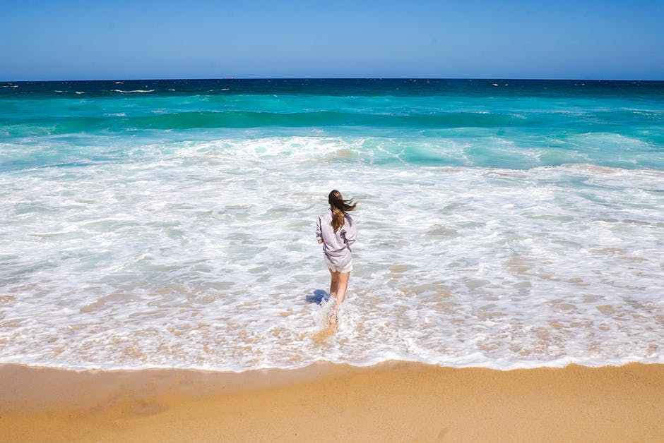 Photo of Woman Standing on Shore Looking at Horizon