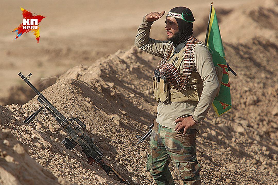 Боец вглядывается в даль из-за насыпи. На спине - флаг. Фото: Александр КОЦ, Дмитрий СТЕШИН