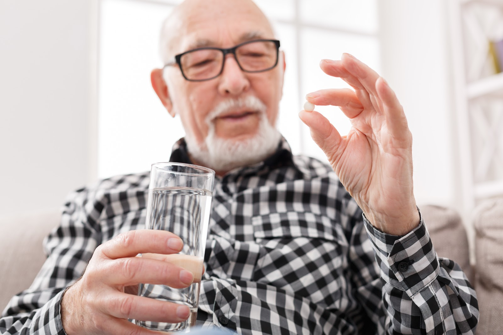 An old man looking at his pill waiting to take it with water