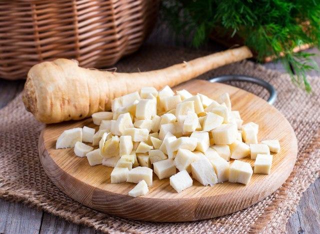 fresh sliced parsnips on wooden board