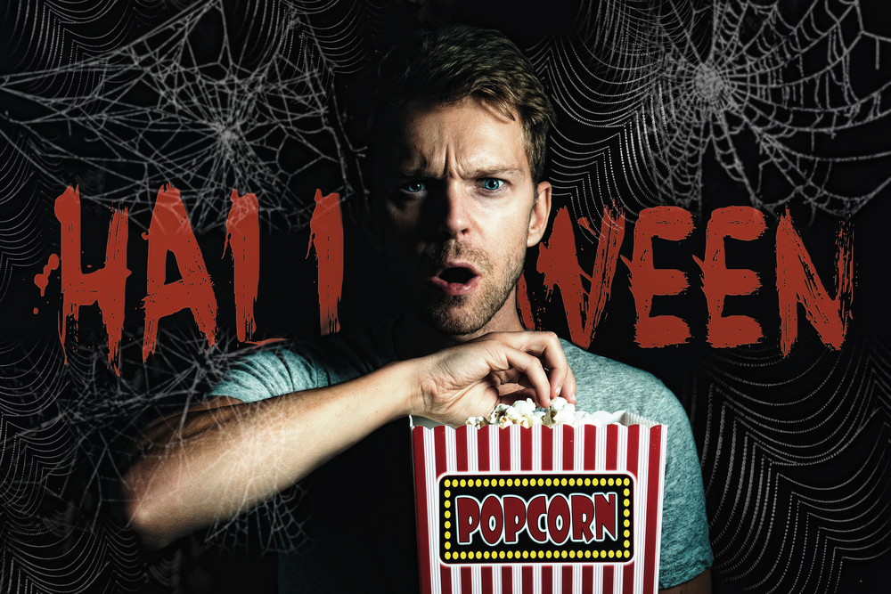 spiderweb on black background with the word Halloween in orange over it and a man in the foreground eating popcorn with a terrified look on his face