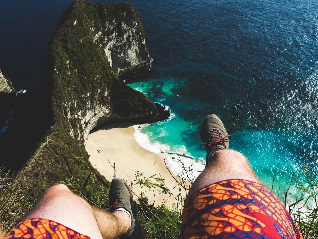 Feet and legs of a man dangling over a cliff and water at Kelingking beach; Bali fitness holiday
