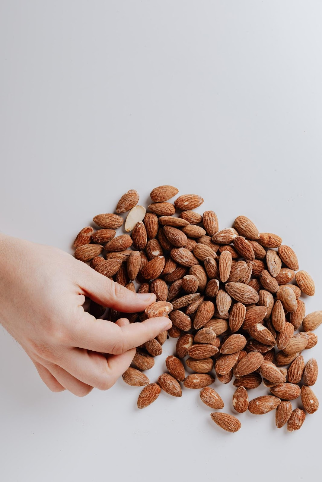 A person holding a handful of coffee beans  Description automatically generated with medium confidence