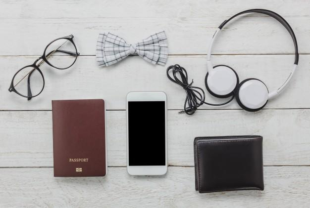 Top view accessoires to travel with man clothing concept. bow tie,passport on wooden background.eyeglasses,headphone,wallet,tree on wood table. Free Photo