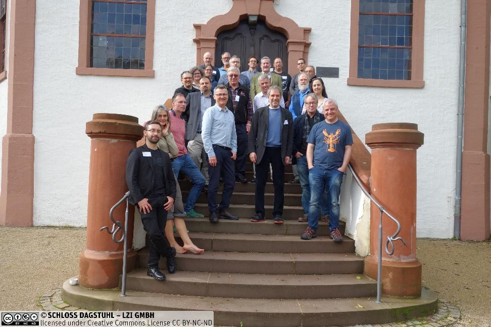 Workshop participants standing in front of the chapel at Schloss Dagstuhl in Wadern, Germany.Description automatically generated