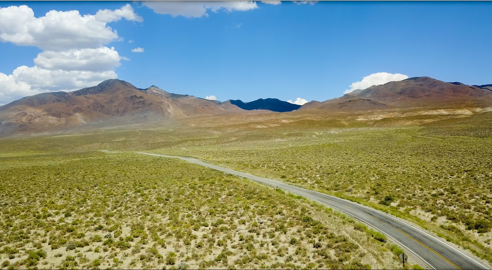 Cycling White Mountain - roadway, meadow, mountains and clouds
