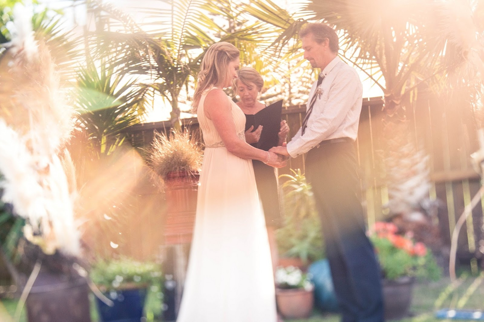 Bride and Groom exchange vows with beautiful sunflare washing over then
