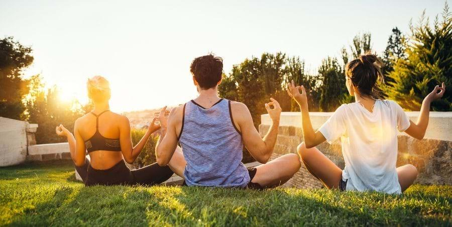 A group of people sitting on grass  Description automatically generated with medium confidence
