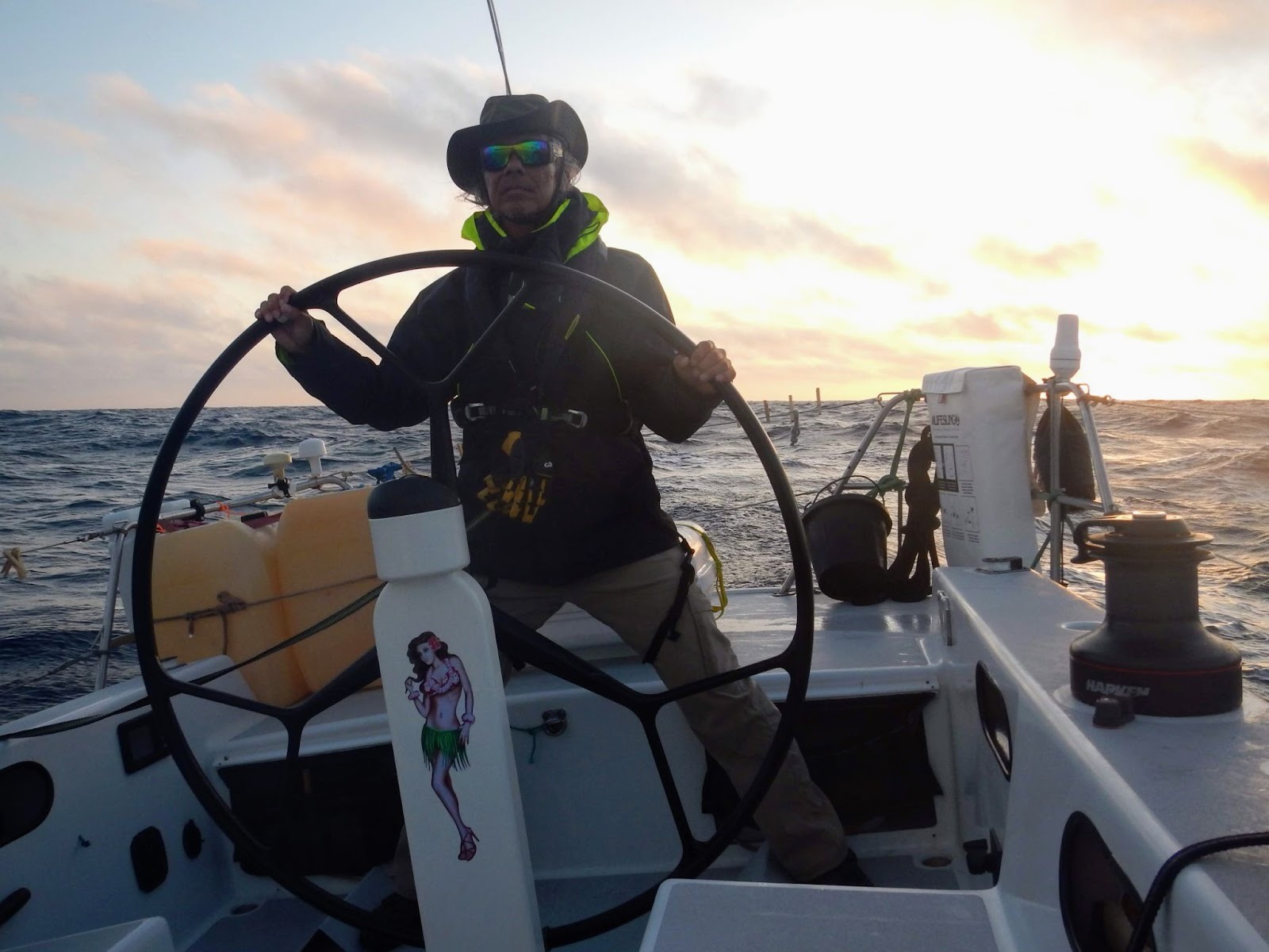 David Wang at the helm of a sailboat on the ocean with the sun setting behind him.