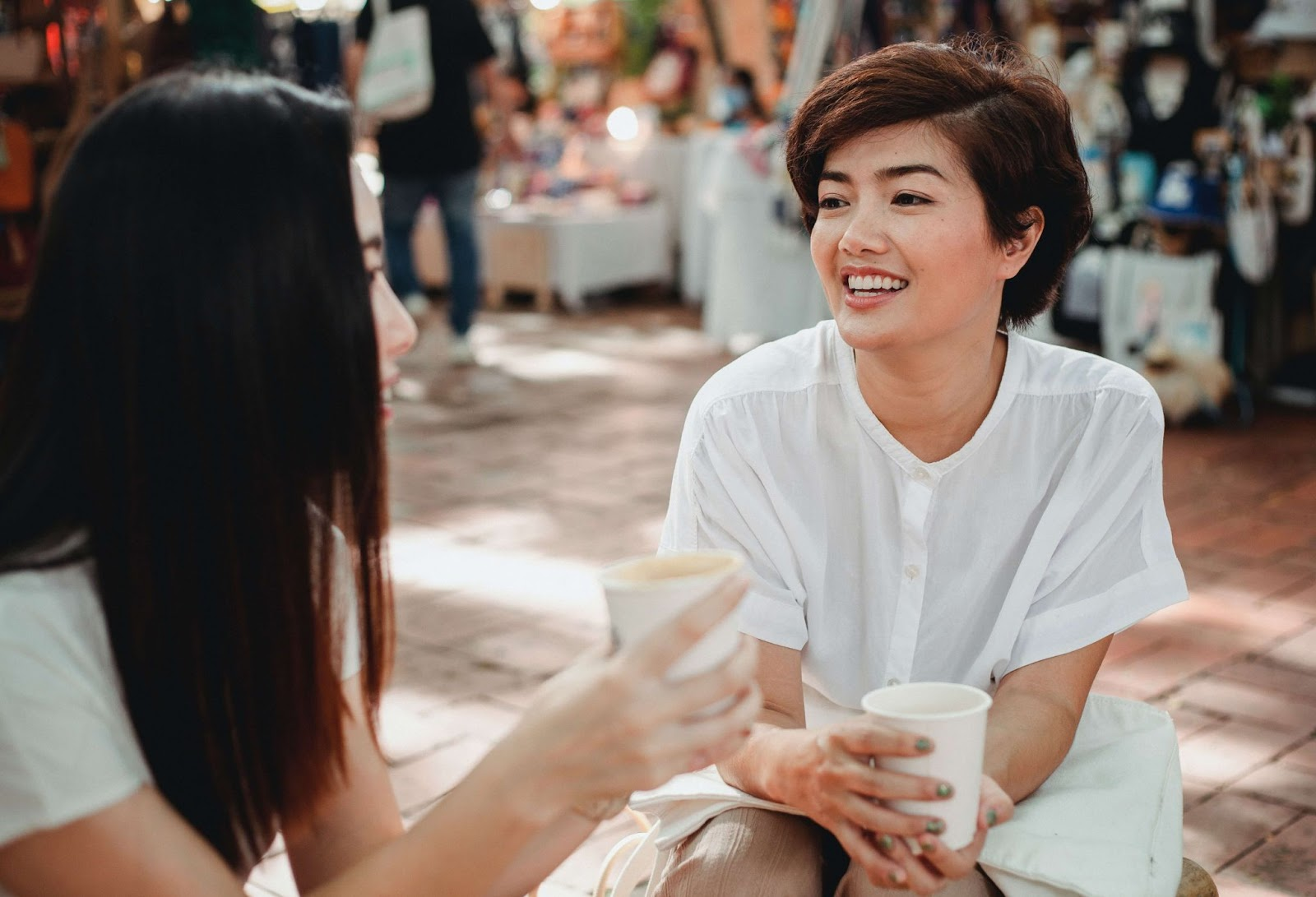 Two women having coffee outside and talking