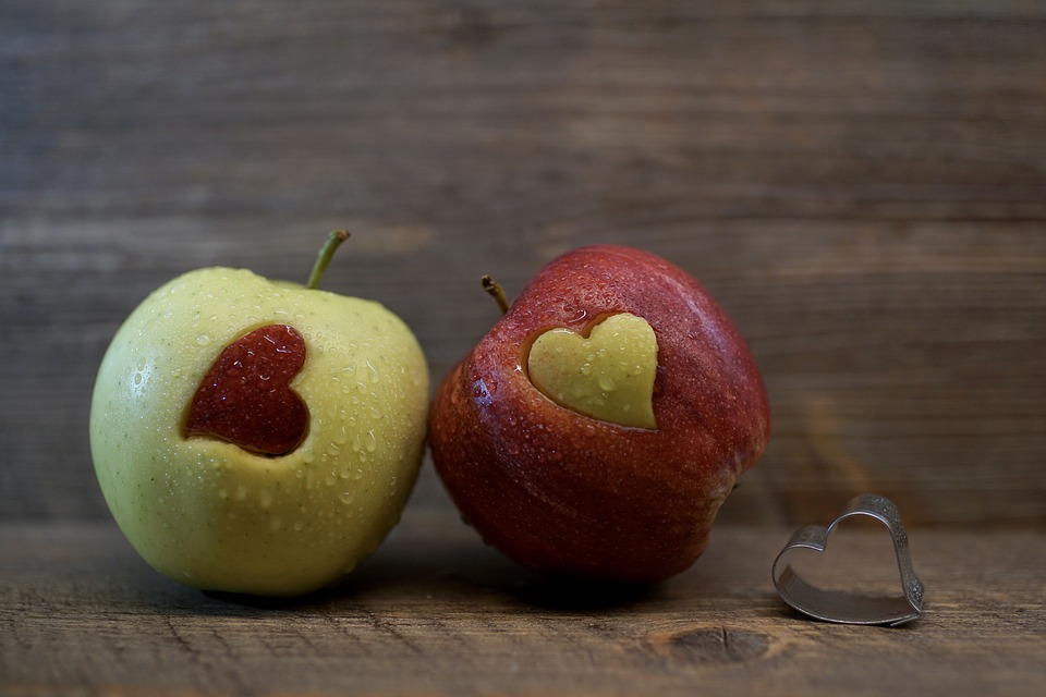 two apples are carved with the figure of hearts