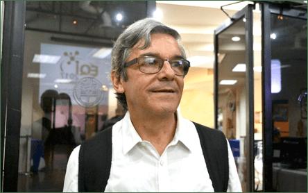 Un hombre con lentes y una tienda  Descripción generada automáticamente