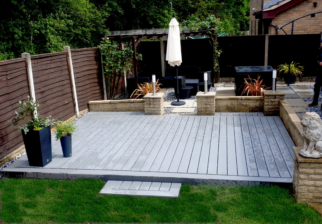 Grey composite decking laid on soil