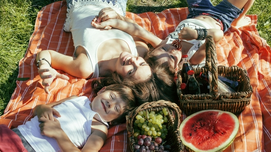 happy family laying on a picnic blanket