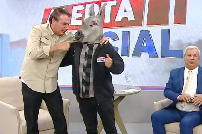 Sem máscara, Bolsonaro está em pé abraçando ao lado um homem vestido com uma cabeça de burro. O apresentador do programa está sentado próximo a eles