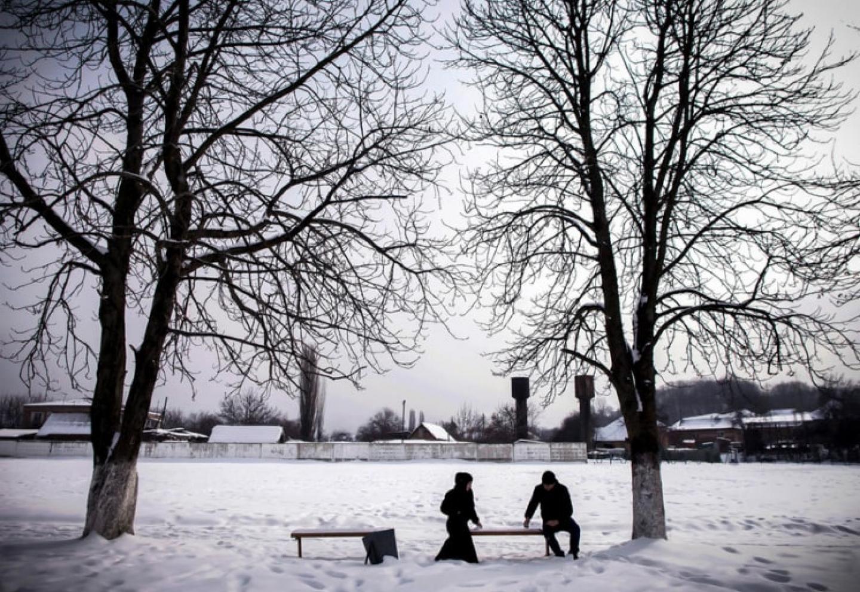 Photo d'un homme et d'une femme assis à distance sur un banc dans un paysage enneigé