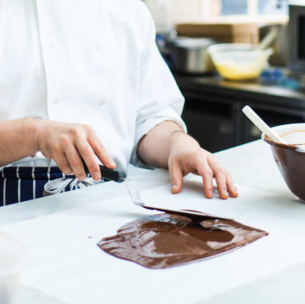Tempered Chocolate Tips; hands spreading chocolate on a butter paper