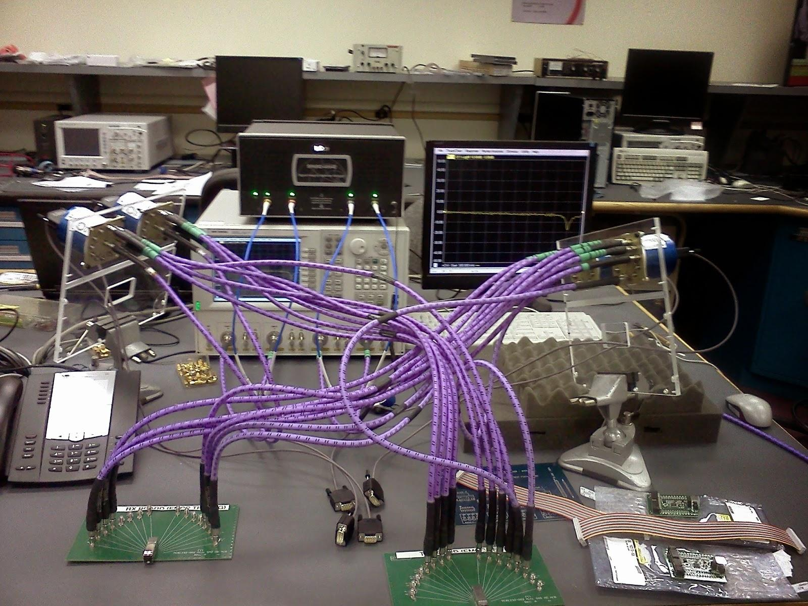 Various lab devices in the background with partially loaded SP12T Radiall switches mounted to a plexiglass frame in the foreground.