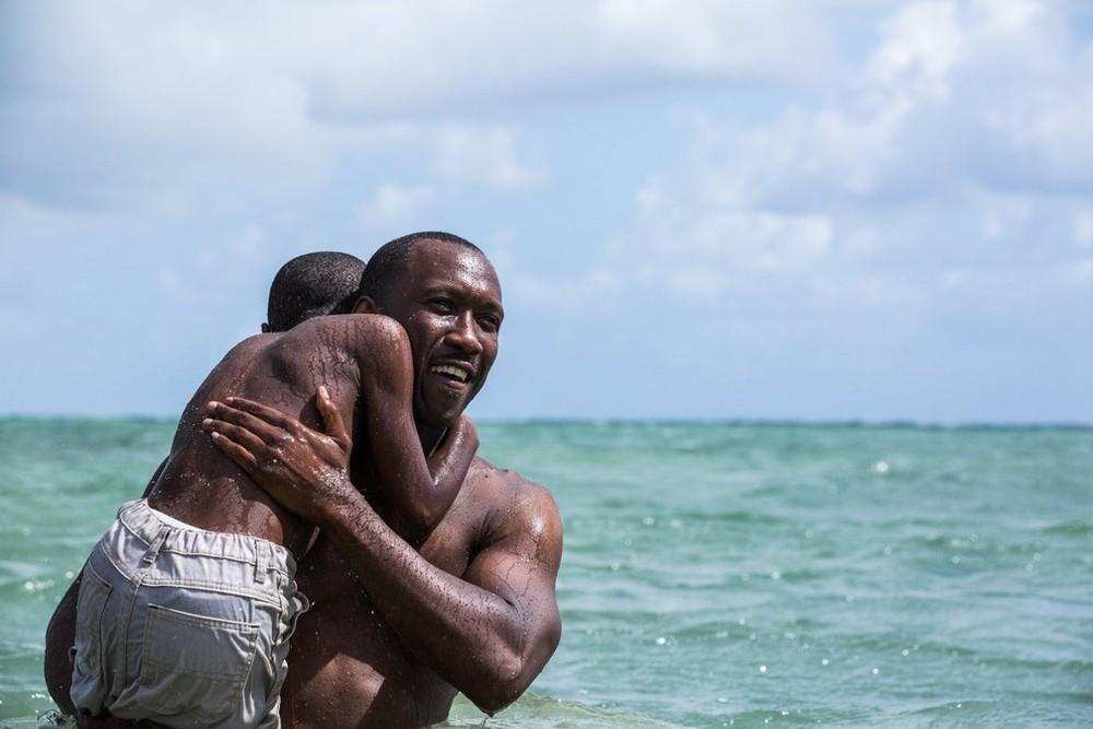 Cena de homem sorrindo segurando criança no colo em alto mar em uma das indicações de filmes para o óscar.