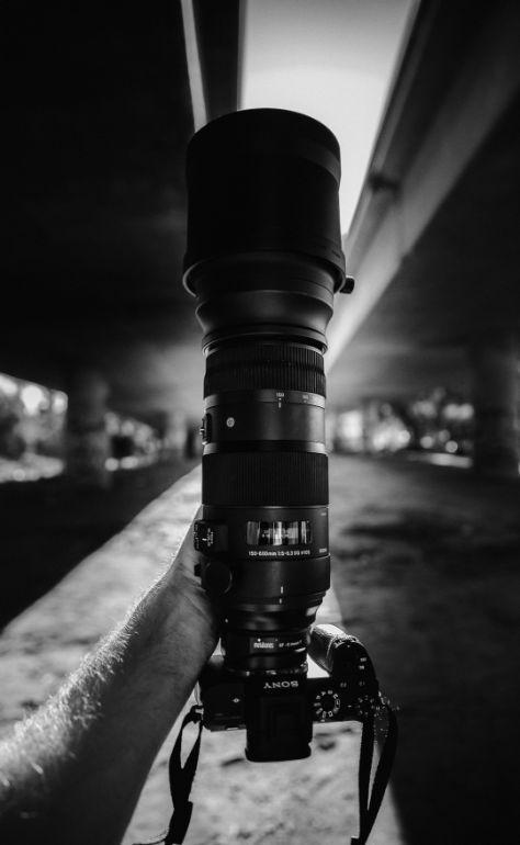 Homen segundo uma camera sony com lente longa