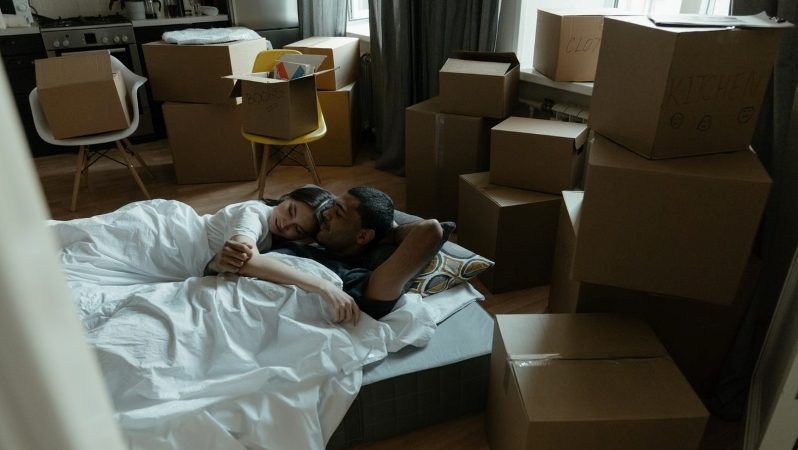 couple sleeping on mattress in new apartment with moving boxes all around