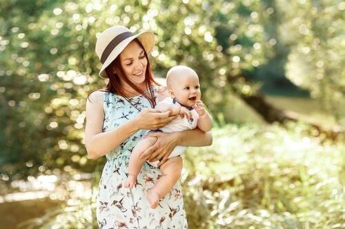 赤ちゃんを抱いて森の中を散歩している母親