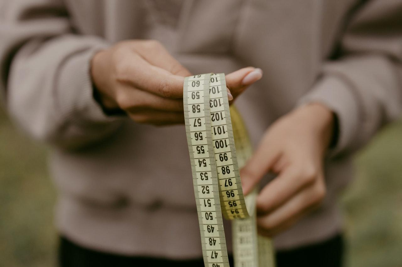 A person holding a measuring tape  Description automatically generated with low confidence