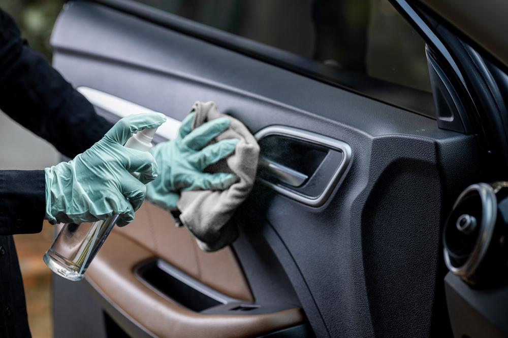 Uma pessoa borrifando algum produto na porta de um carro com um pano e luvas.