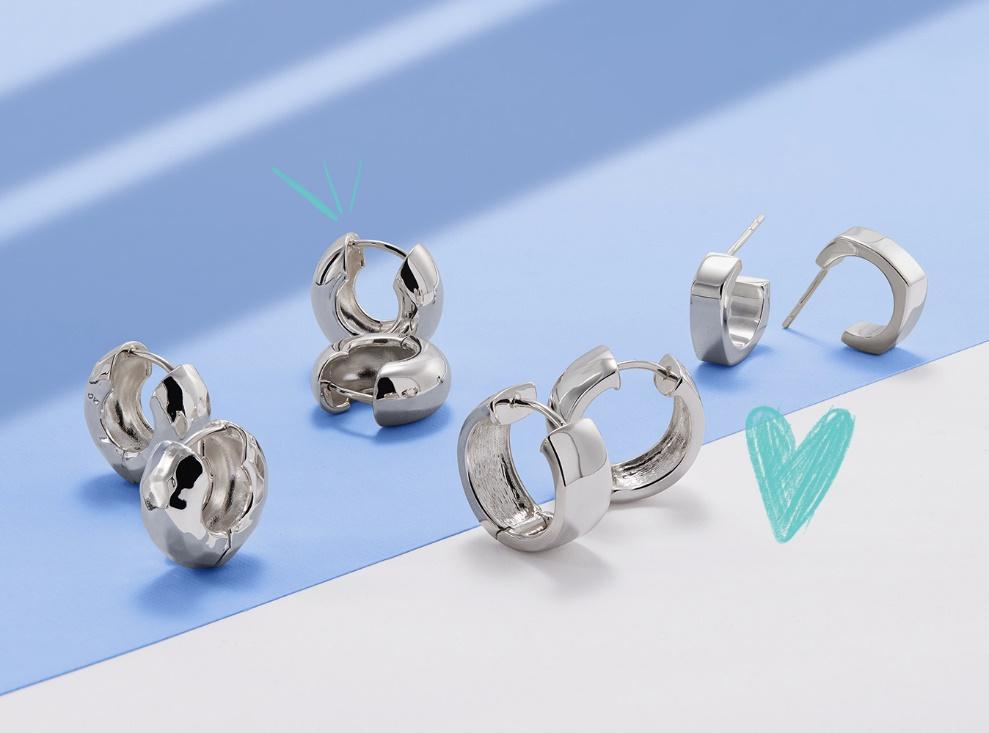 Sterling silver huggie earrings on blue background.