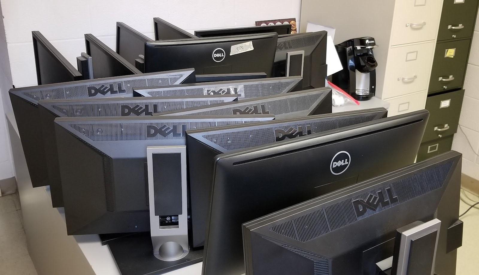 Image: more than a dozen computer monitors, waiting to be packed and shipped back to Princeton