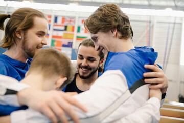 Male gymnasts in huddle in gymnasium