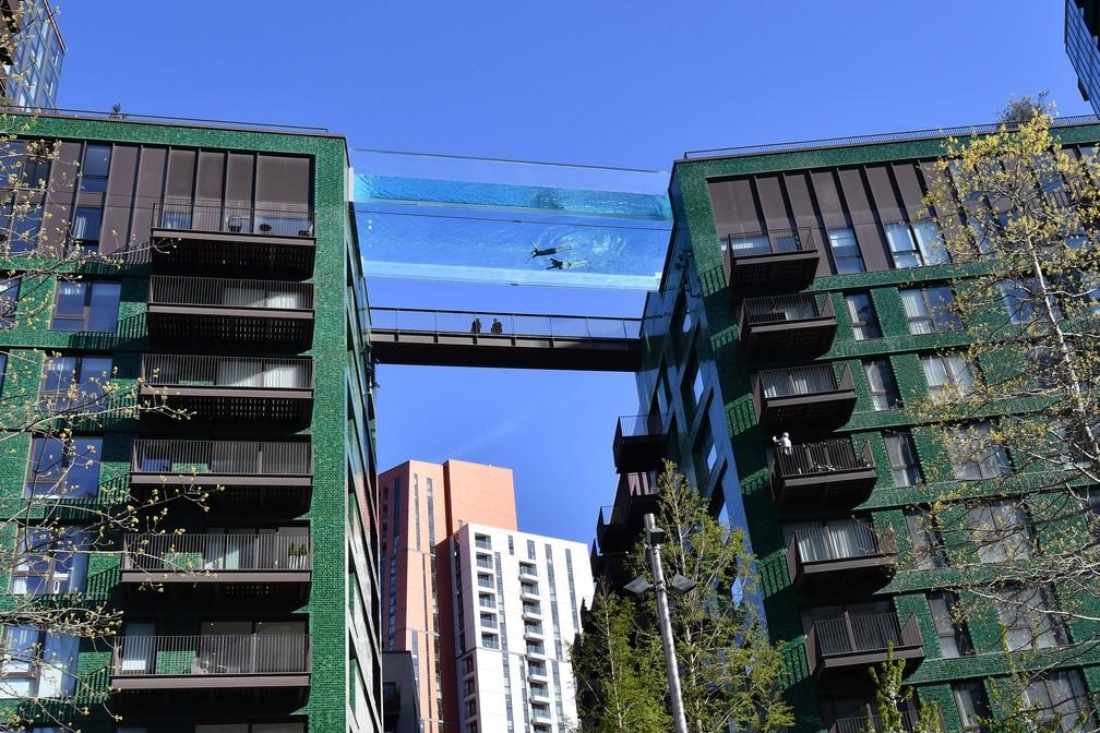 Modelo nada em uma piscina de acrílico transparente fixada entre dois blocos de apartamentos em Embassy Gardens, em Londres. — Foto: Justin Tallis/AFP
