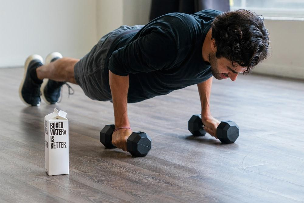 man in black t-shirt and black shorts doing push up