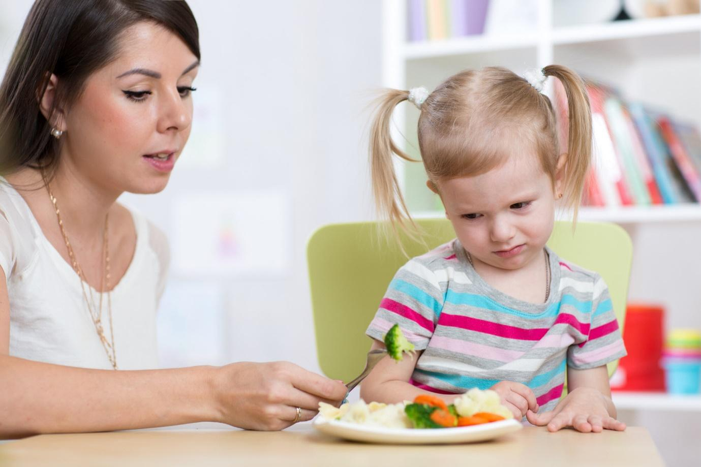 A person feeding a child a piece of food  Description automatically generated with low confidence
