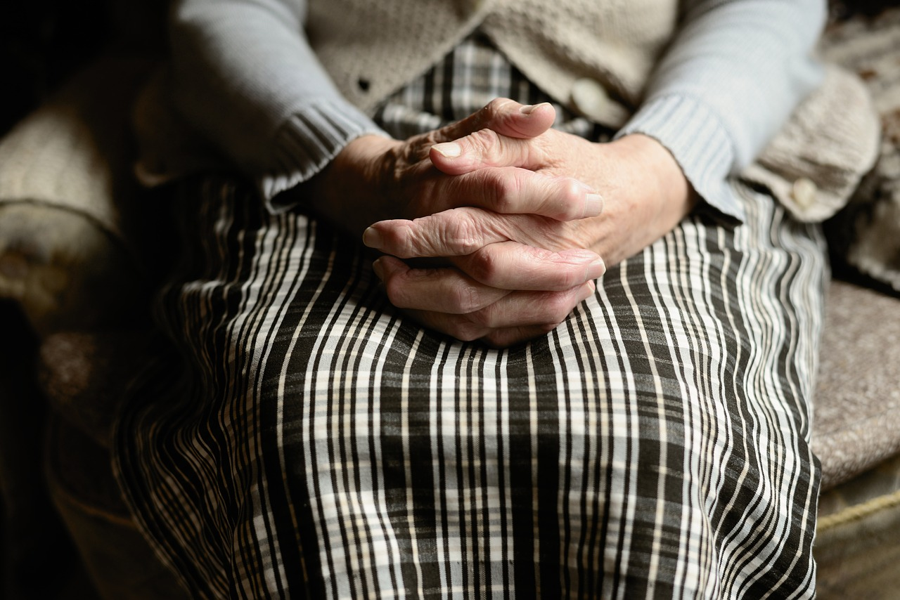 An old woman sitting with her hands on her lap, portraying aging.