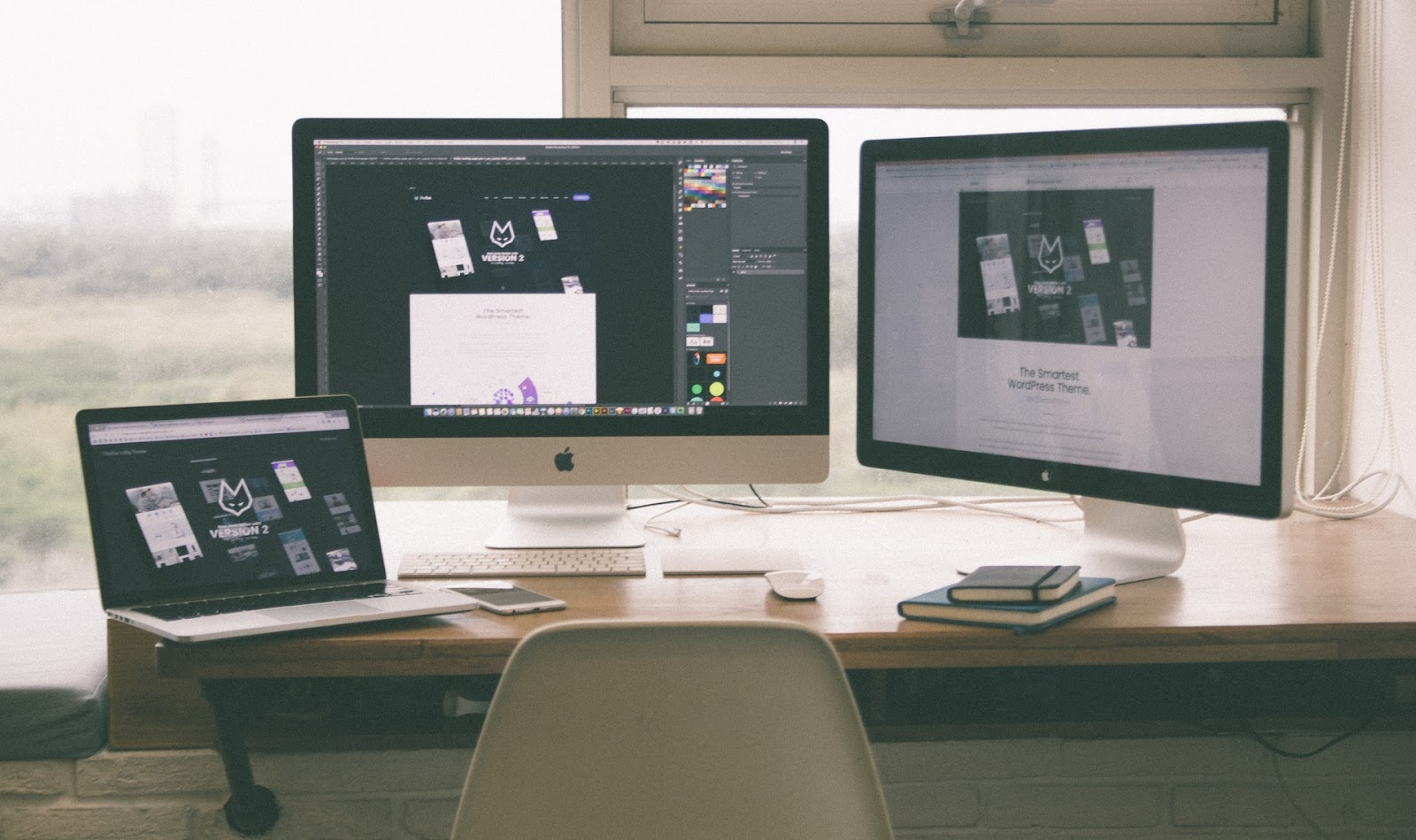 A freelancer's desk with three screens ready to design a graphic for Instagram.