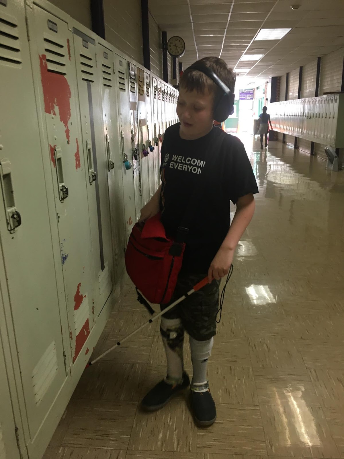 Eddie wears hearing protection and carryies a bookbag while using a cane to navigate a hallway full of lockers at school