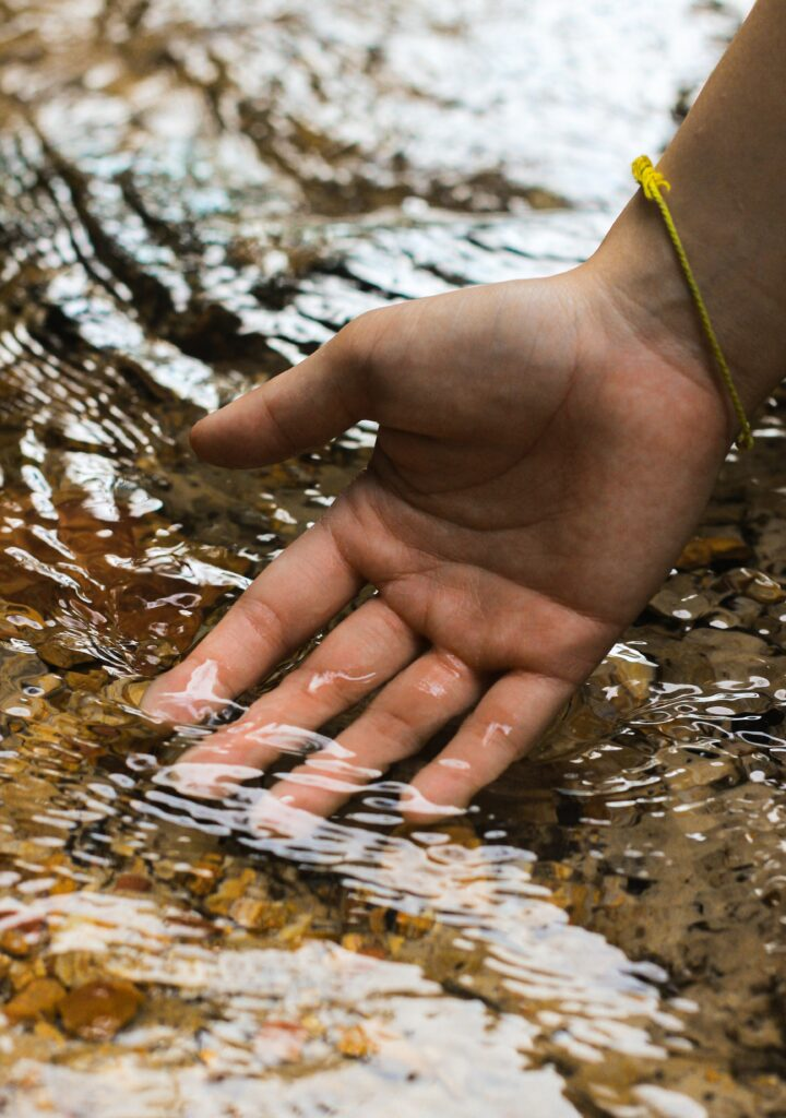 an open hand immersed in what appears to be a shallow river