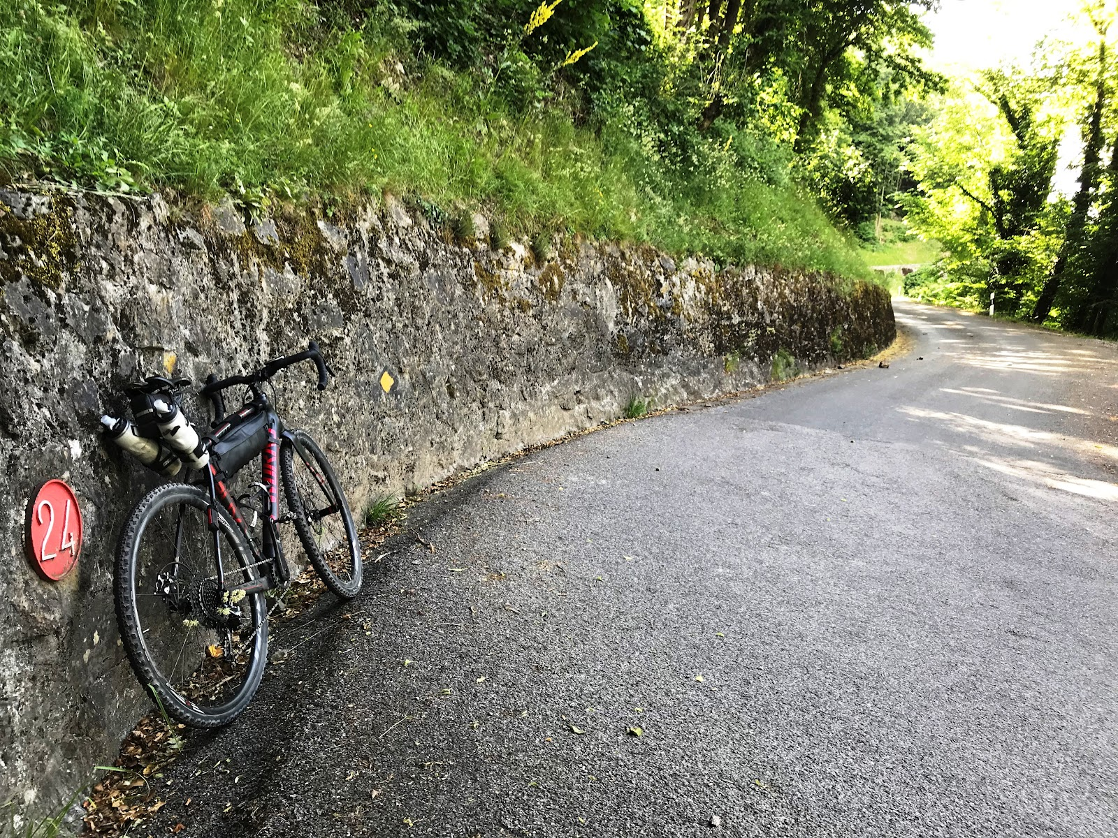 Cycling Rionda - bicycle leaning against wall, hairpin 24 sign and road