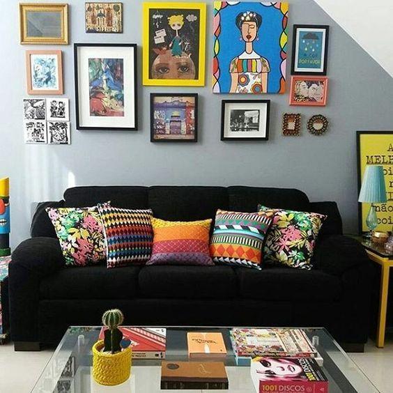 Sala com sofá preto, almofadas estampadas coloridas, parede com bastantes quadros coloridos e mesa de centro de vidro com livros.