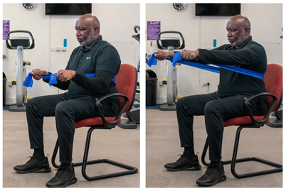 seated with resistance band wrapped around back with the ends held out infront of chest.