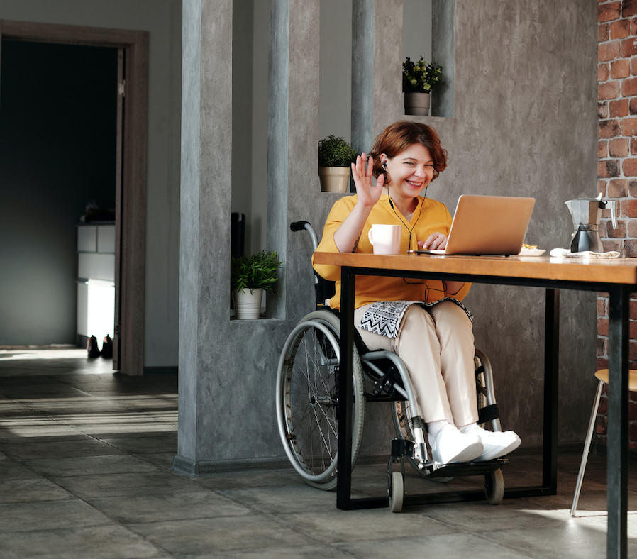 Woman in wheelchair smiling and waving to laptop