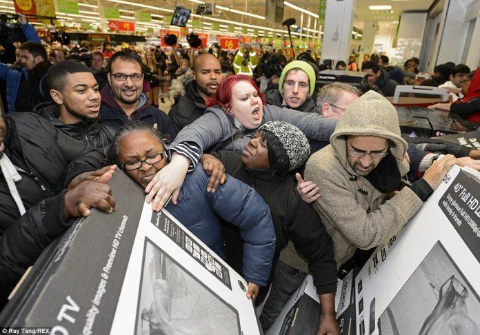 Fotografia de um aglomerado de pessoas tentando alcançar algumas televisões em uma loja durante uma Black Friday.