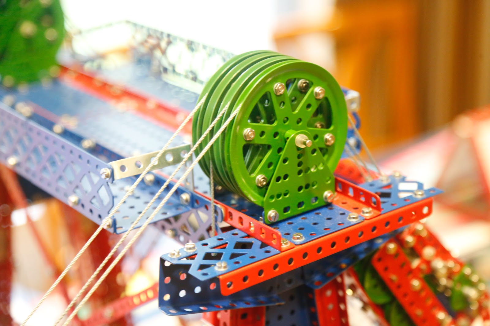 This is a close up view of a pulley and cables attached to a children's engineering toy that looks similar to the popular Erector Set.