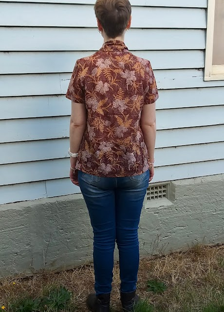 Siobhan stands in front of a blue weatherboard wall. She wears an earthy brown, fern-print short sleeve blouse with comically large bow at neck, blue slim jeans and brown boots. Her back is to the camera.