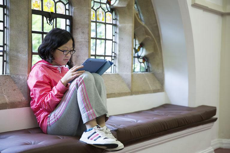 Student reading on a window seat in Bell St Albans